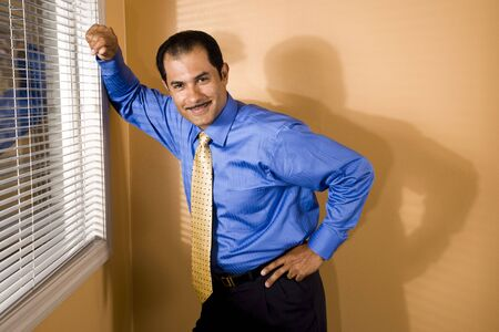 Confident middle-aged Hispanic businessman talking by office window with hand on hip photo