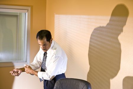 the sleeve: Middle-aged Hispanic businessman rolling up sleeve looking down reading in boardroom