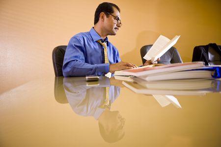 reference book: Mediana edad empresario de hispanos que trabajan en la oficina leyendo el libro de referencia