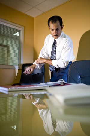 rolling up: Middle-aged Hispanic businessman working in office rolling up sleeves looking down at paperwork