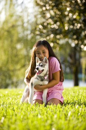 yards: Pretty young Asian girl hugging Alaskan Klee Kai puppy sitting on grass Stock Photo