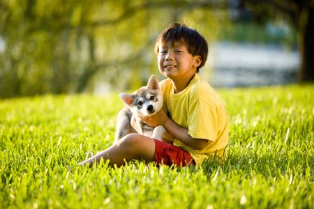 Young Asian boy holding Alaskan Klee Kai puppy sitting on grass photo
