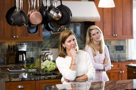 Mid-adult woman and teen daughter standing in kitchen Stock Photo - 6865105