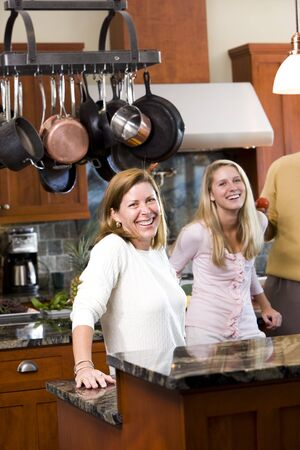 Mid-adult woman and teen daughter standing in kitchen Stock Photo - 6865066