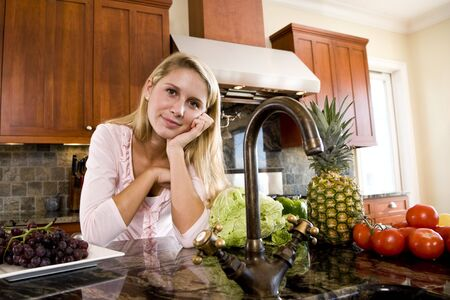 Seventeen year old girl leaning on kitchen counter Stock Photo - 6865116