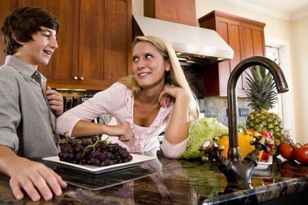 Teenage children in kitchen with fruits and vegetables on counter Stock Photo - 6865073