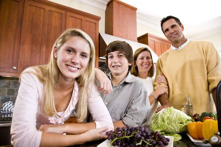 Happy family with two teenagers standing together in kitchen