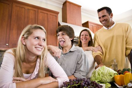 teenage boy: Happy family with two teenage children making funny faces in kitchen