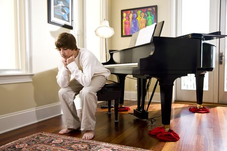 Serious fourteen year old boy at home sitting on piano bench looking down photo