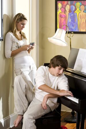 ignoring: Teenage siblings ignoring each other, one texting, the other playing piano