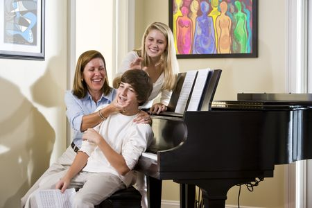 teasing: Family sitting on piano bench, mother teasing teenage son