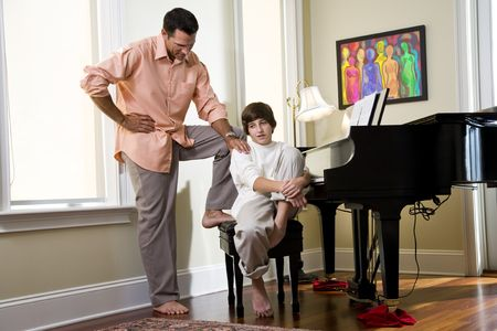 Seus father talking to teenage son at home by piano Stock Photo - 6865099