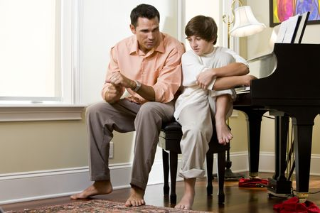 father and son: Serious father talking to teenage son at home by piano