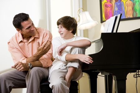 Father with teenage son at home talking together photo