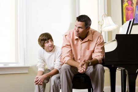 Father with teenage son at home sitting together on piano bench, boy looking up to dad photo