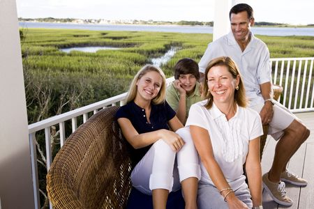 balcony: Family with teenager children on vacation sitting together on terrace Stock Photo