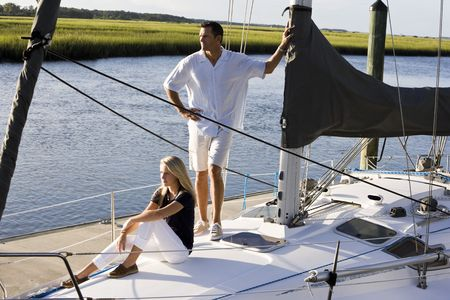 intercoastal: Father and teenage daughter relaxing on sailboat at dock on sunny day - Florida intercoastal waterway