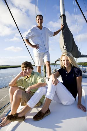 Father and teenage children relaxing on sailboat at dock on sunny day photo