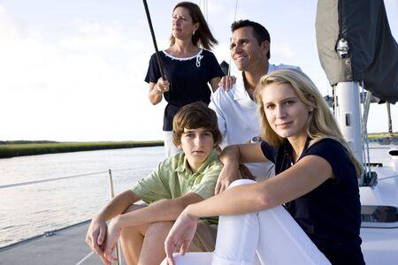 bambini seduti: Famiglia con figli adolescenti, seduta sulla barca al dock in giornata di sole  Archivio Fotografico