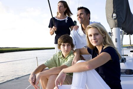 Family with teenage children sitting on boat at dock on sunny day photo