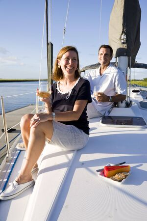 boating: Mid-adult couple sitting on deck of boat enjoying drink