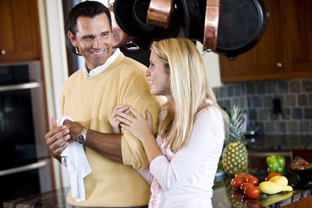 Close father and teenage daughter chatting in kitchen photo
