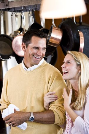 Close father and teenage daughter talking and laughing together in kitchen photo