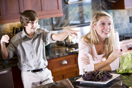 Teenage girl daydreaming in kitchen, brother pointing at her from behind Stock Photo - 6865070