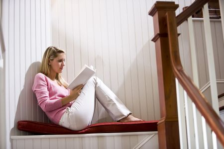 quietly: Teenage girl quietly relaxing and reading book by staircase at home