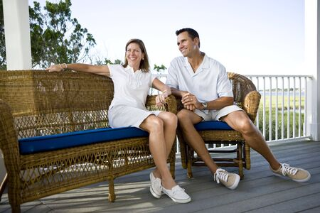 balcony: Happy mid-adult couple sitting together on terrace on vacation