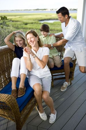Smiling family sitting and laughing together outdoors on terrace