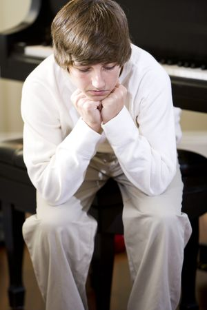 Sad 14 year old teenage boy sitting with chin on hands at home on piano bench Reklamní fotografie - 6865122