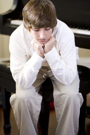 Trieste 14-jarige tiener jongen zitten met kin op handen thuis op piano bank  Stockfoto - 6865122