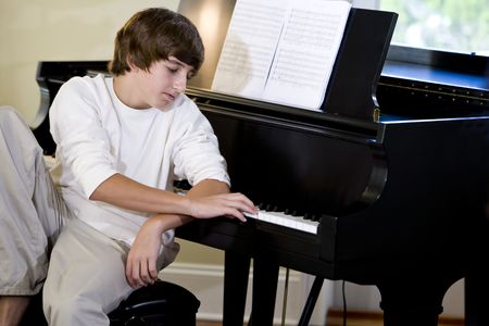 Serious 14 year old teenage boy looking down at piano keys, thinking Stock Photo - 6859050