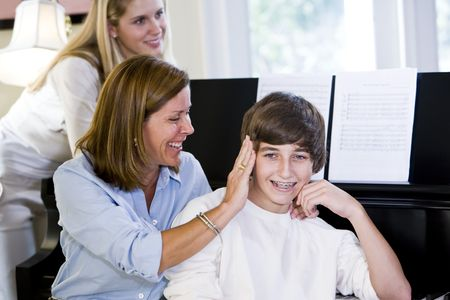 Mother and sister affectionately teasing teenage boy at home by piano Stock Photo - 6865026