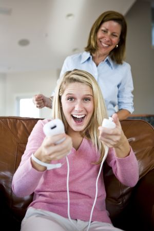 Excited teenage girl playing video games at home with mother behind photo