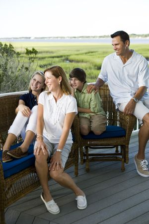 Family of four sitting together outdoors on terrace with view of Florida intercoastal waterway photo