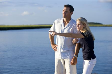 Teenage girl and father standing by water watching and pointing photo