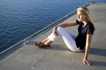 Pretty teenage girl sitting on dock by water watching and thinking photo