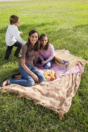Little boy and two sisters having picnic in park photo