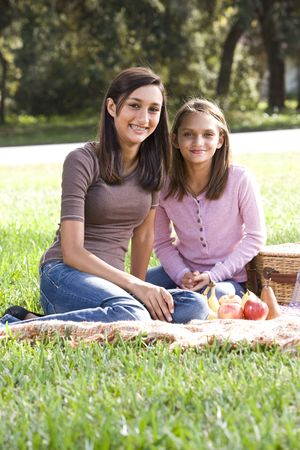 Sisters sitting on picnic blanket in park photo