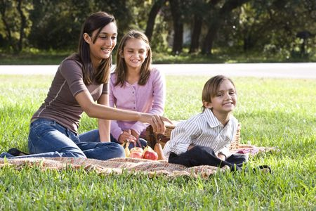 10 years girls: Two sisters and little brother playing on picnic blanket in park Stock Photo