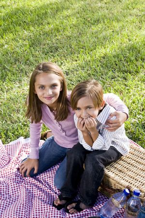 Little boy and big sister sitting on picnic blanket in park photo