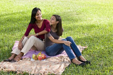 indian kid: Close mother and daughter sitting on picnic blanket looking at each other Stock Photo