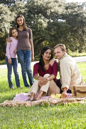 multiracial family: Interracial family with two children having picnic on sunny day in park Stock Photo