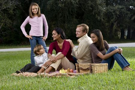 Affectionate interracial family with three children enjoying a picnic together in park photo