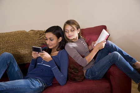 younger: Teen girl texting on mobile phone while younger sister looks over her shoulder Stock Photo