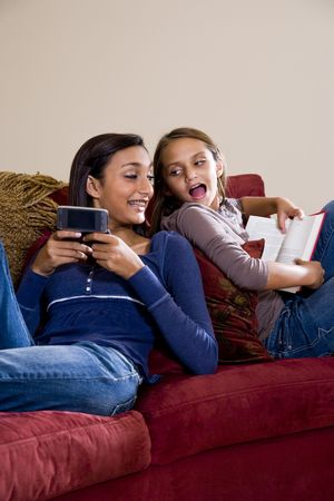 Teen girl texting on mobile phone while younger sister reads book photo