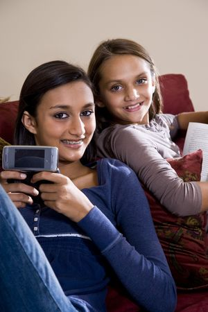 Teen girl texting on mobile phone while younger sister looks over her shoulder photo