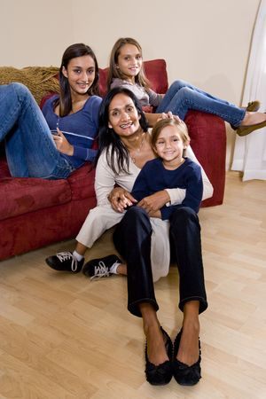Family portrait of Indian mother with 3 mixed-race children sitting at home together on sofa photo